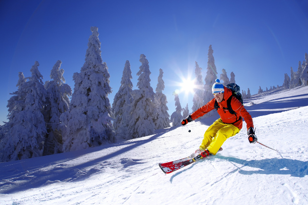 Skier skiing downhill in high mountains against sunshine.