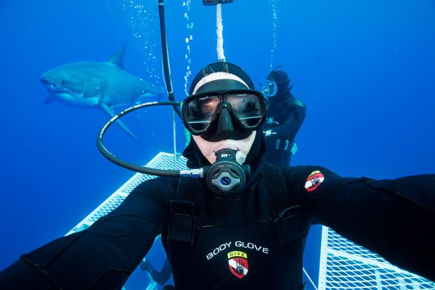 Photographer David Fleetham takes a selfie before entering the cage with a great white shark in the background near Guadalupe Island, Mexico. Image: David Fleetham / Barcroft India / Barcroft Media via Getty Images
