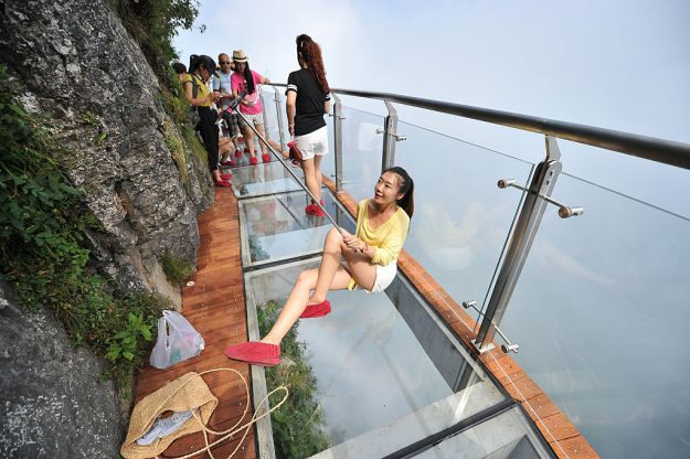 A tourist takes a selfie on the glass skywalk on the cliff of Tianmen Mountain in Zhangjiajie National Forest Park, China. Image: VCG/Getty Images