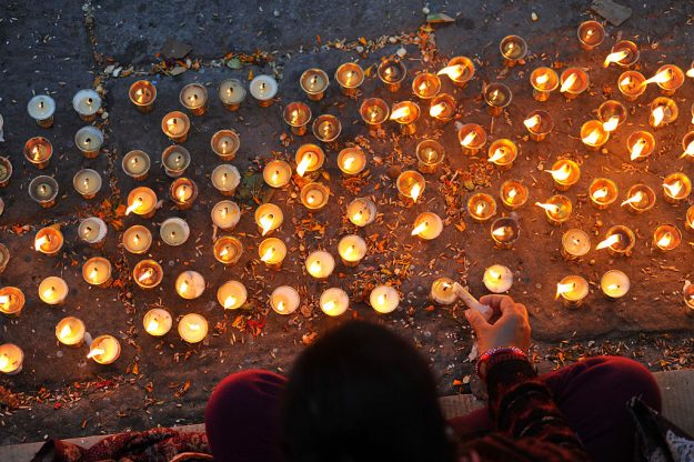 Nepalese devotees offering 108 butter lamps on the bank of Bagmati river.