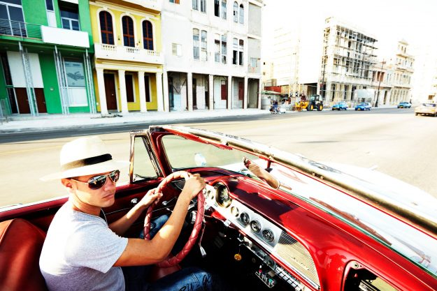 Man driving a 1950s car in Havana, Cuba. Image: Mark Read/Lonely Planet