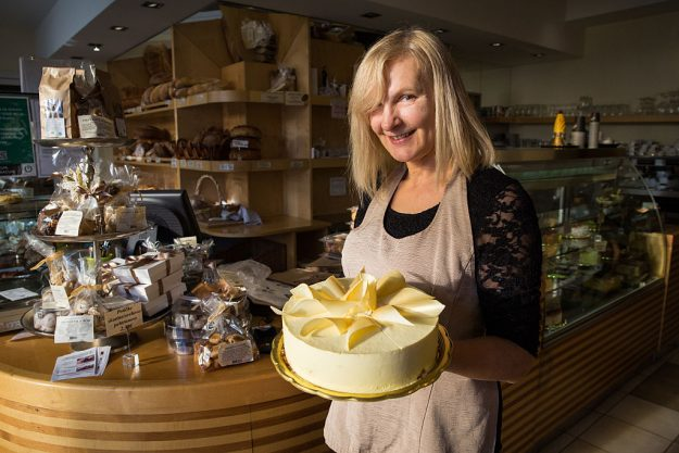 Bakery worker Jelenc Darja is pictured holding a white chocolate cake with gold decoration called 'Melanija'.