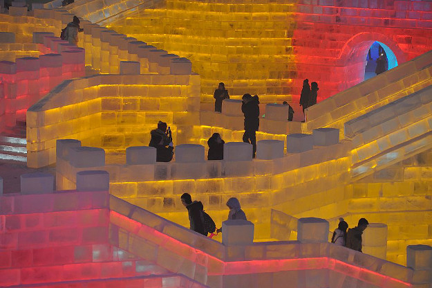 People visit the ice sculptures illuminated by coloured lights.
