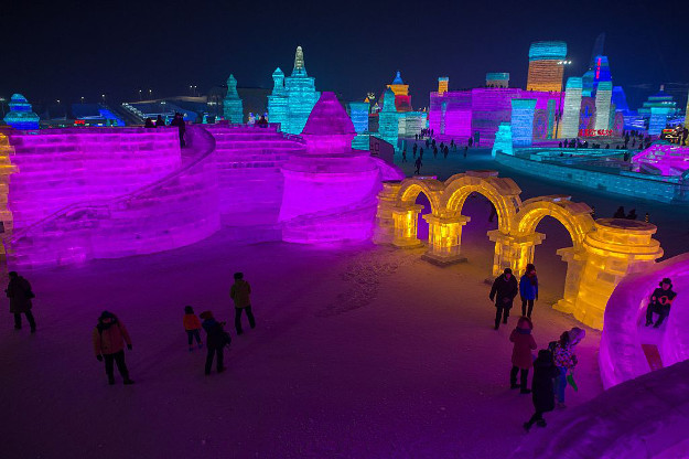 People visit ice sculptures illuminated by coloured lights at the Harbin Ice and Snow Festival to celebrate the new year in Harbin on January 4.