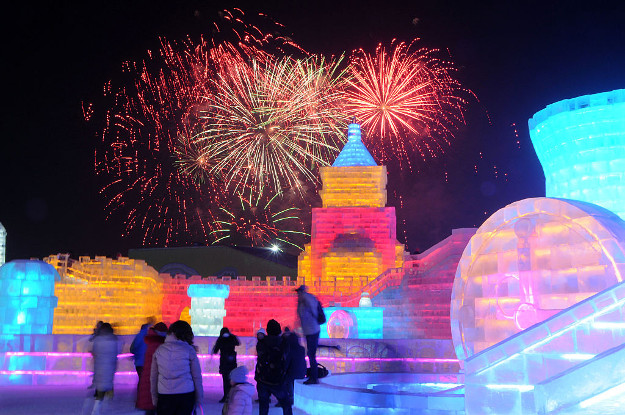 Tourists visit ice sculptures illuminated by coloured lights.