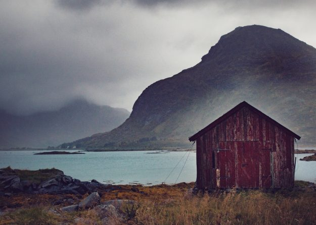 A shack with peeling paint sitting abandoned in north Norway.