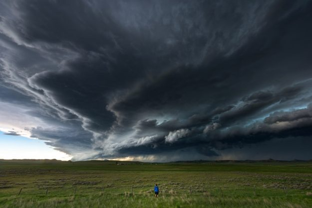 A storm chaser stands in a field near Cheyenne, Wyoming watching a tornadic supercell approach.