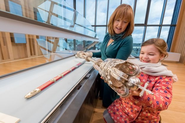 Museum Curator Grace Fegan and Bea Ni Dhrisceoil from St Canices National School in the Kilkenny Room which houses the pure silver Civic Sword and Mace dating back to 1609.