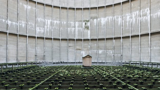 A booth sits still amidst fern in a decommissioned cooling tower in Belgium.