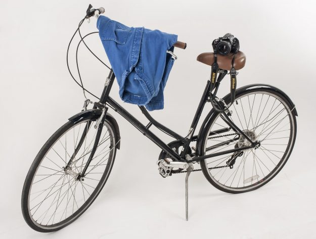 Bicycle, used by Bill Cunningham, ca. 2002; jacket, used by Bill Cunningham, 2000s, camera (Nikon Model D5200) with 24 mm, lens (AF Niccor) and strap, used by Bill Cunningham, ca. 2012.