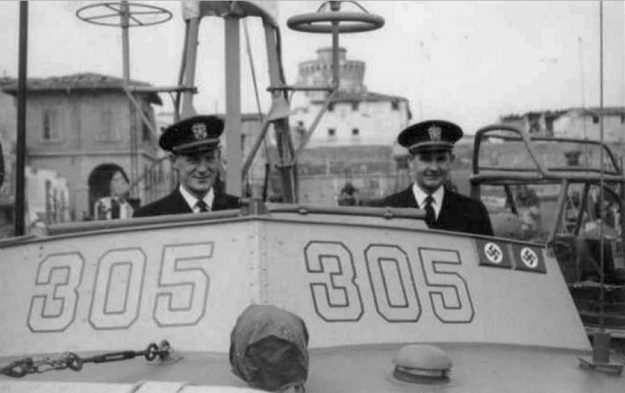 """Ensign Bleeker Morse (left) and Lieutenant Junior Grade Allan Purdy on the bridge of PT-305 in Leghorn (Livorno), Italy, on March 16, 1945. The """"kill plaques"""" on the chart house signify the two enemy craft sunk by PT-305 to that date. Gift of Joseph Brannan."""