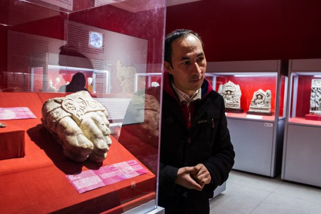 Ghulam Ali Mohseni , curator of Numismatic at the National Museum stands by the foot of Zeus artefact.