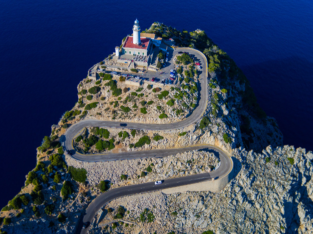 Crowning a Mediterranean cliff, the Formentor Lighthouse stands atop a serpentine ribbon of Mallorcan asphalt.