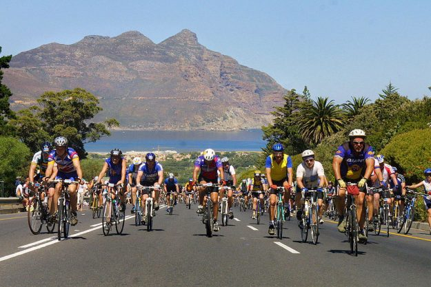 Cyclists climb Suikerbossie Hill with Chapman's Peak in the background.