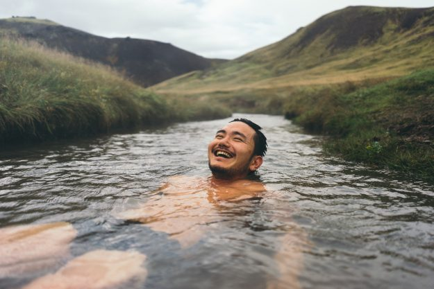 Man soaking in natural hot spring surrounded by nature in Iceland...and looking pretty happy about it.