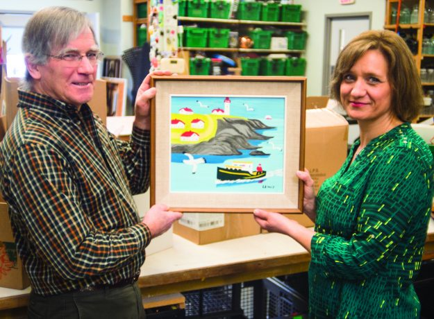 Volunteer Louis Silcox and General Manager Karla Richards display the original Maud Lewis painting discovered at the New Hamburg Thrift Centre. Image: MCC Photo/Ken Ogasawara