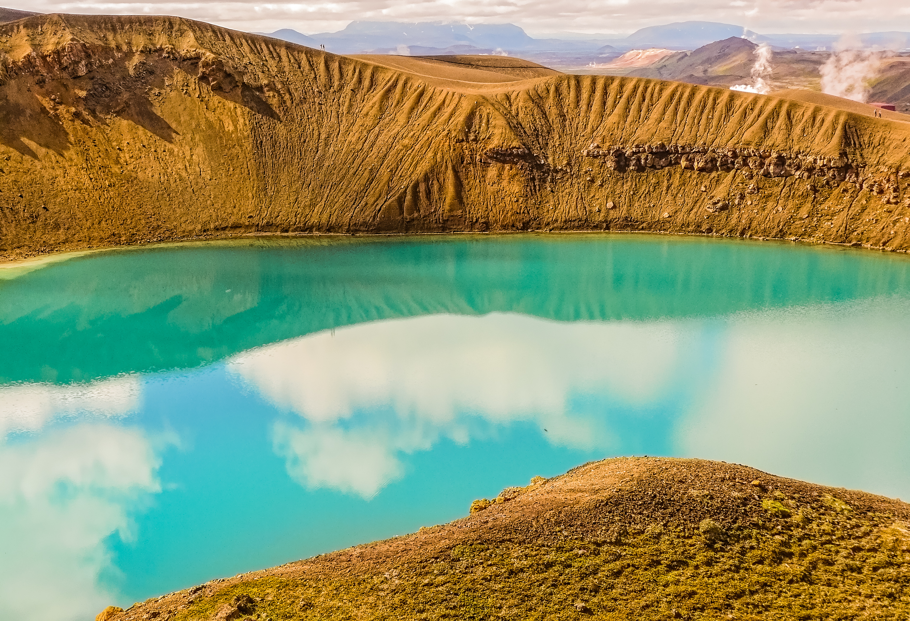 Askja is a volcano in the remote highlands of Iceland. Viti is an explosion crater which now contains a geothermal lake of mineral-rich, opaque blue water that is warm enough for swimming.