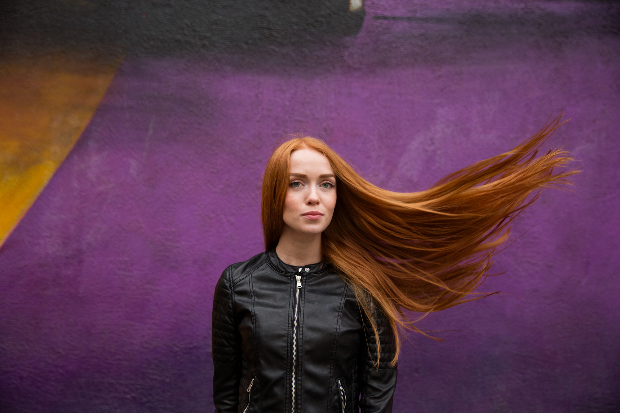 A redhead model Marina photographed in Moscow Russia in front of a purple mural