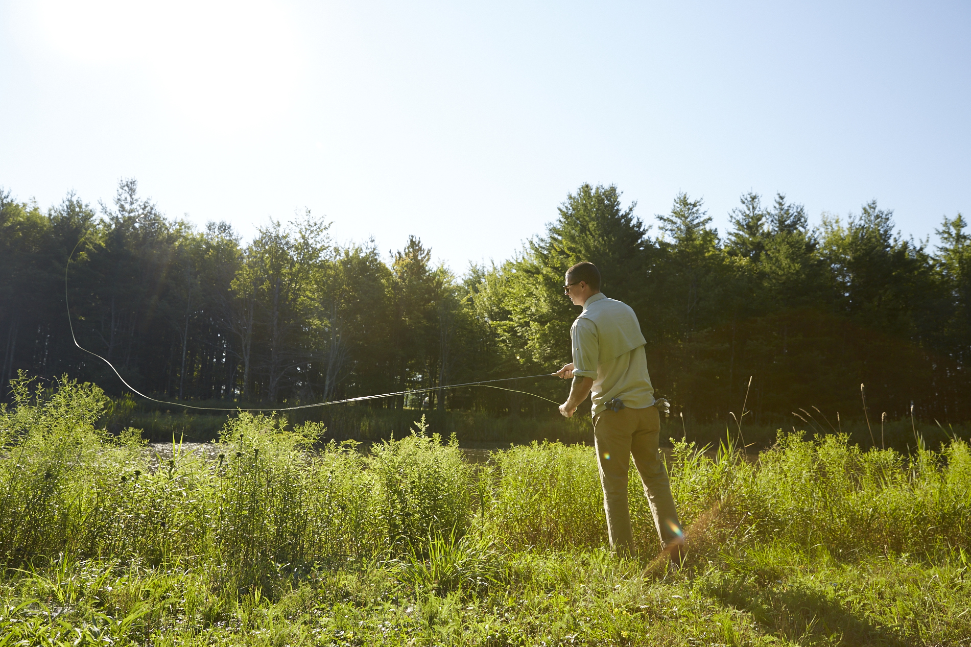 A man fishes at a river at a tentrr campsite in the US