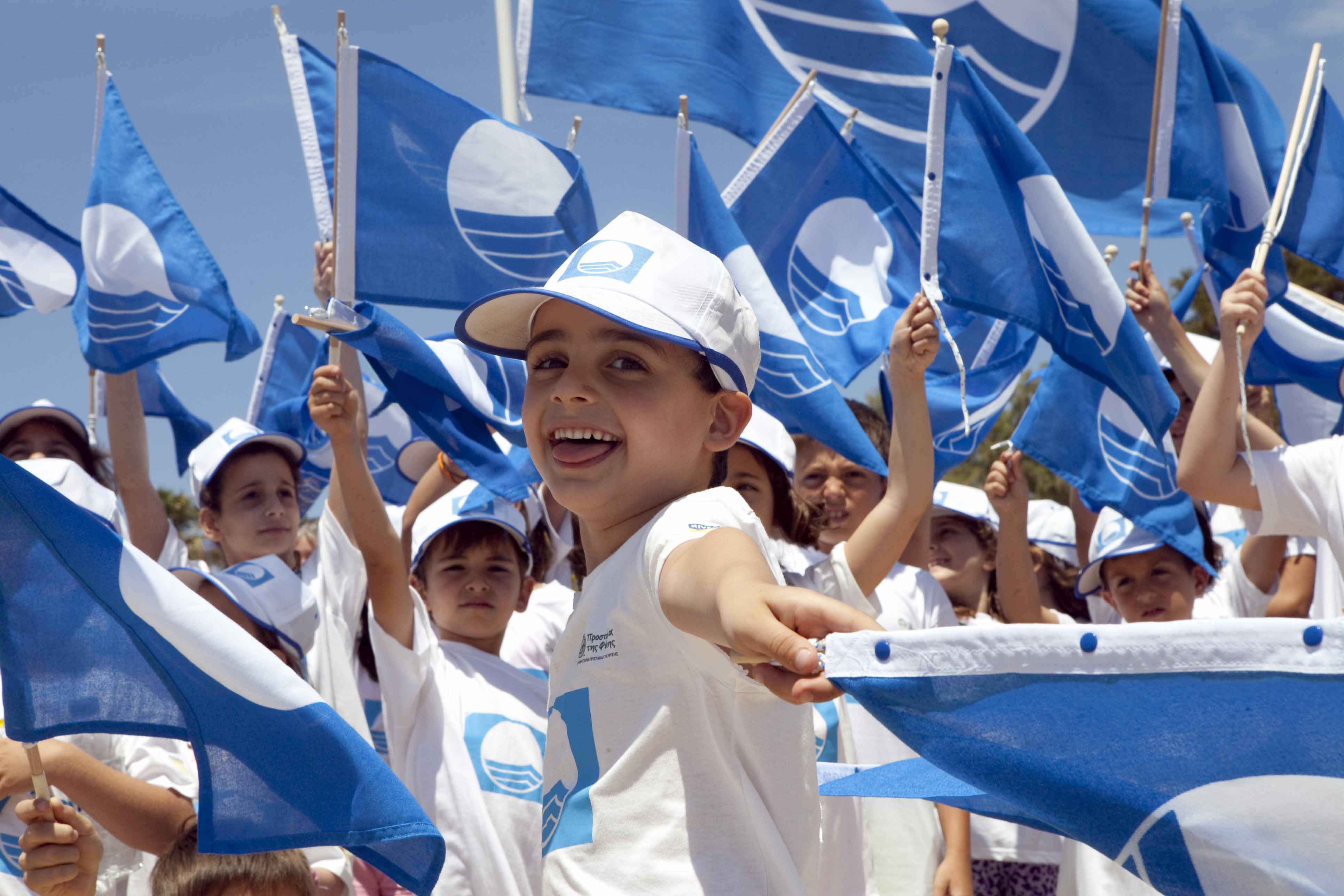 Young children with blue flag beach flags