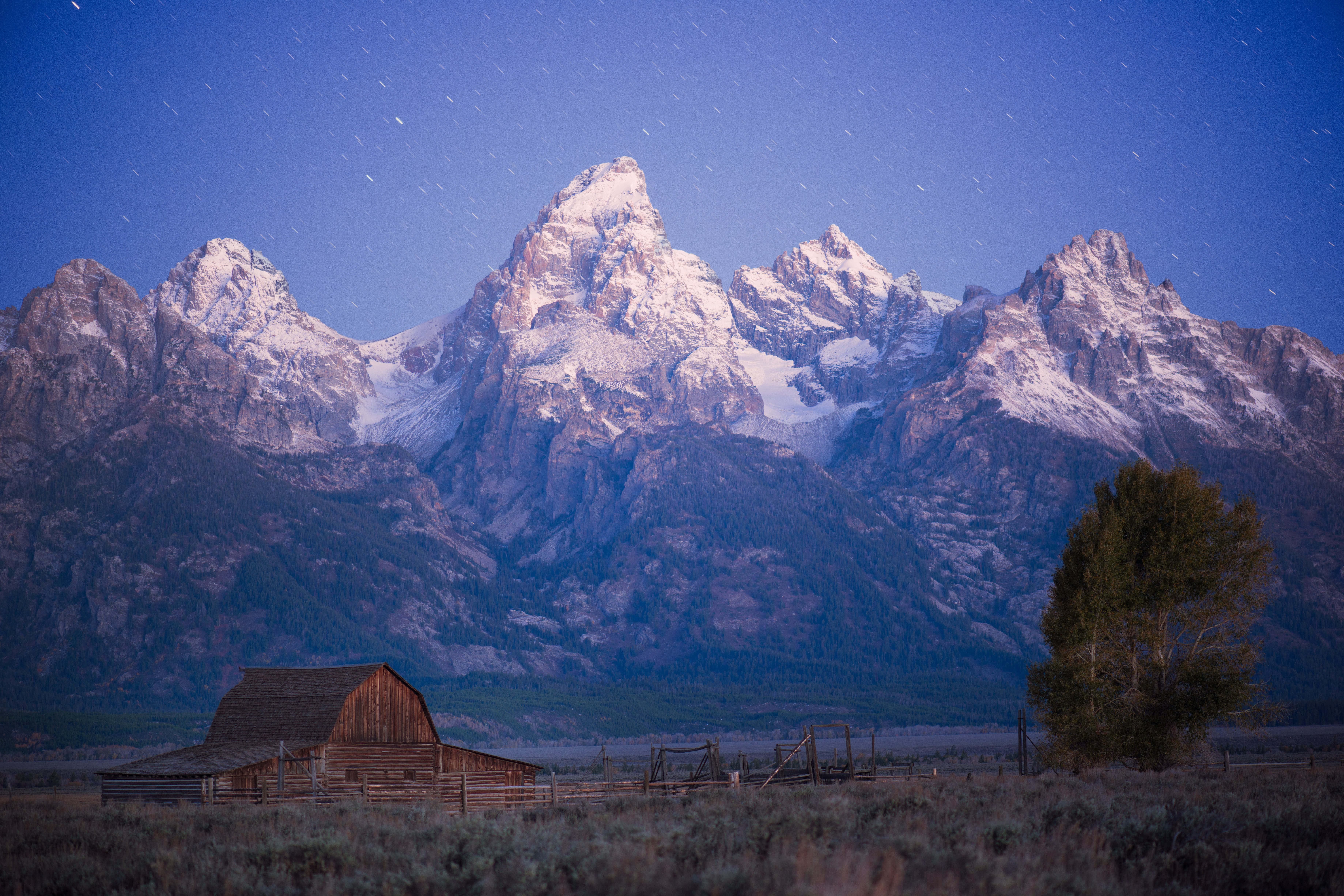 Deep blue twilight skies with fading stars appear above rugged Grand Teton and the famous John Moulton Barn in Grand Teton National Park, Wyoming.