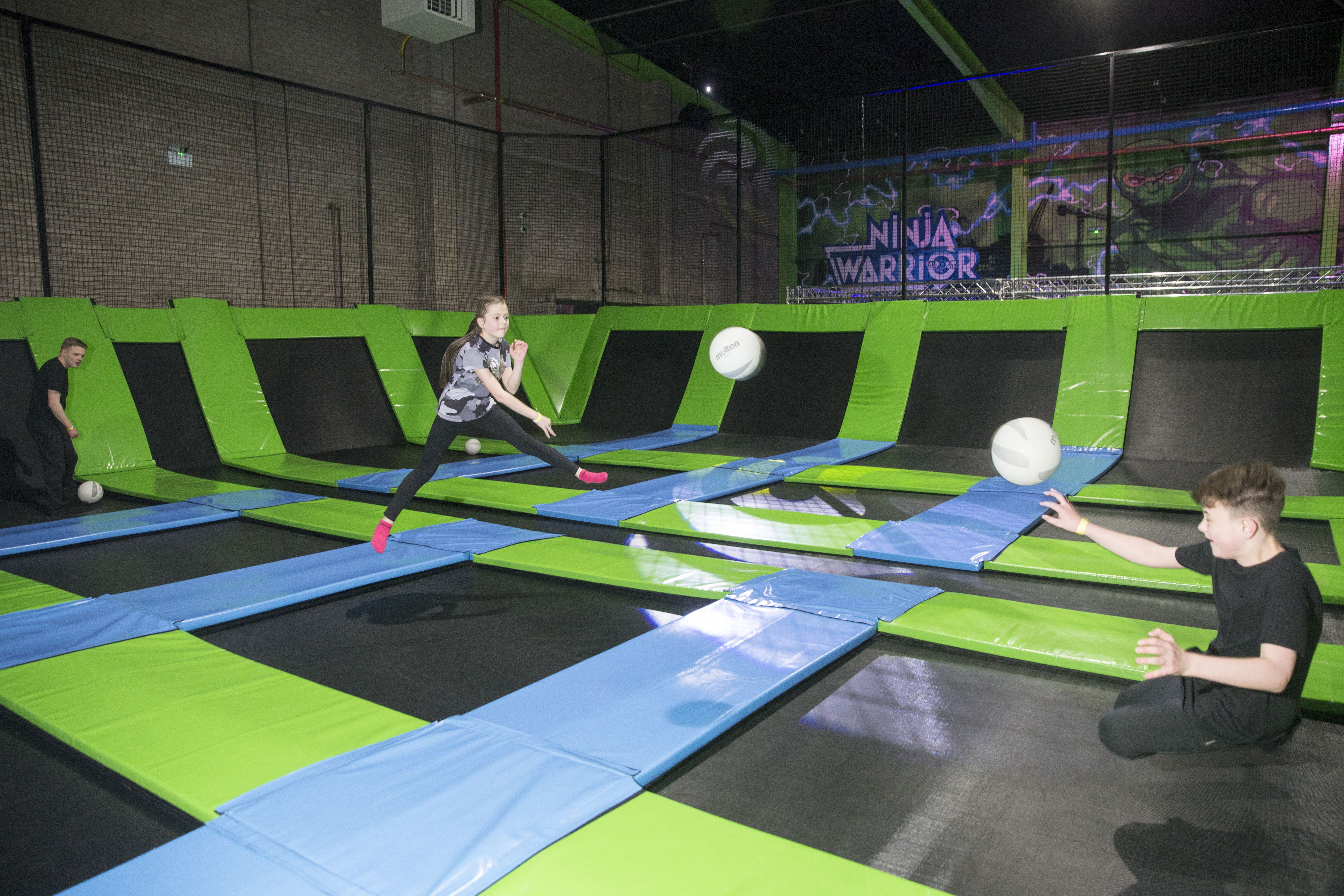 Children playing trampoline soccer