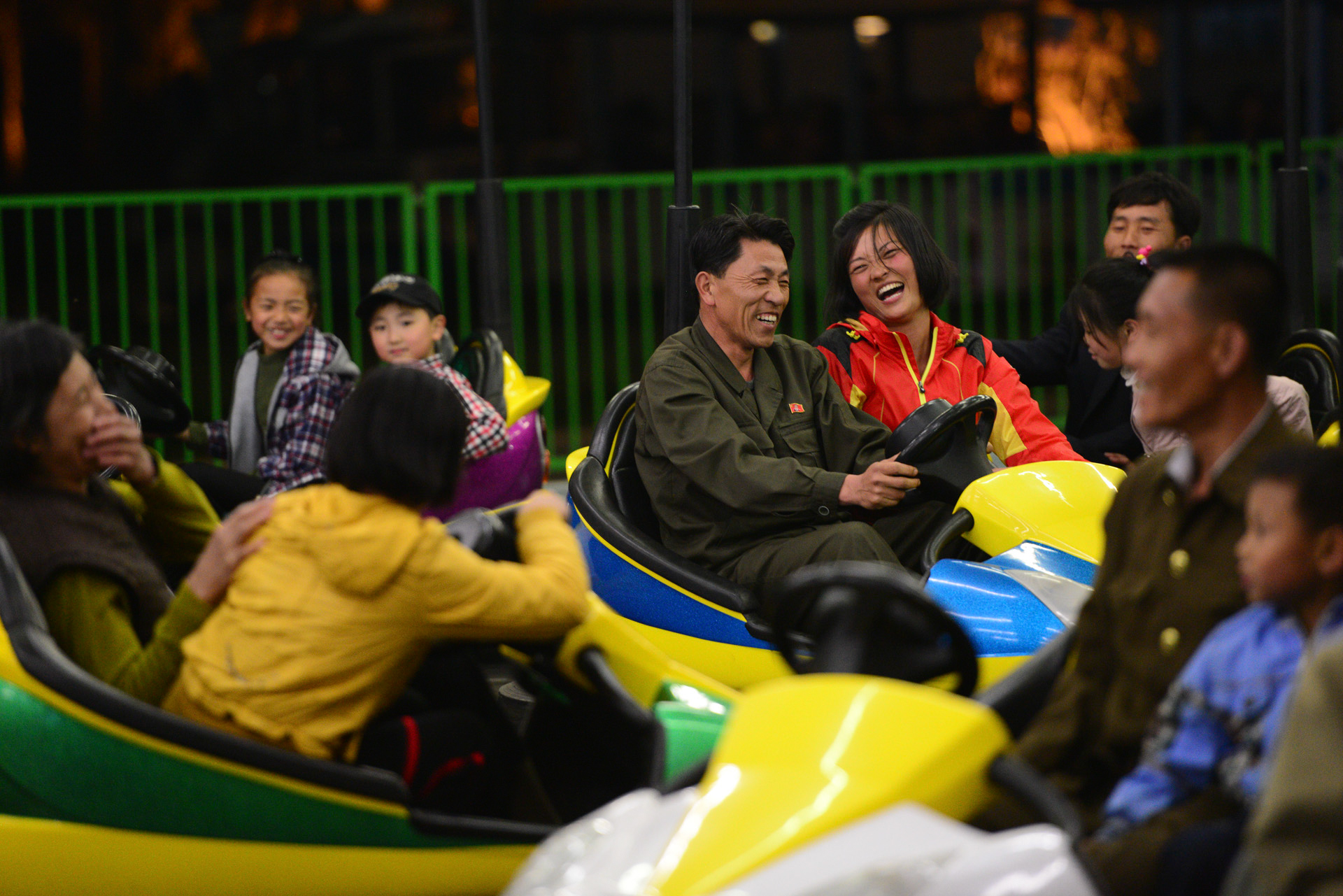 Two people share a laugh at the Pyongyang Amusement park, which featured bumper cars, a roller coaster and other rides.