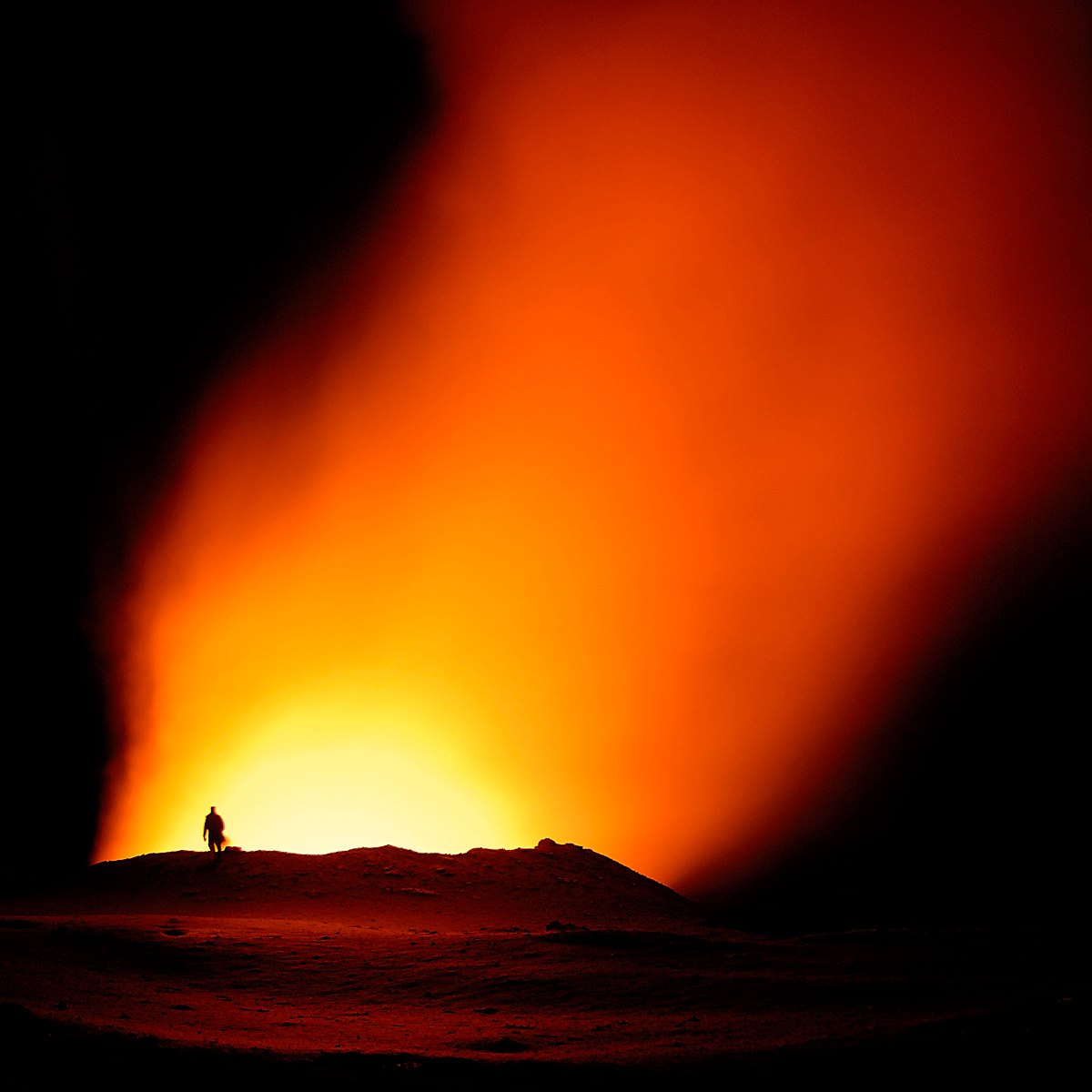 On the edge: hiker looking into a volcano crater