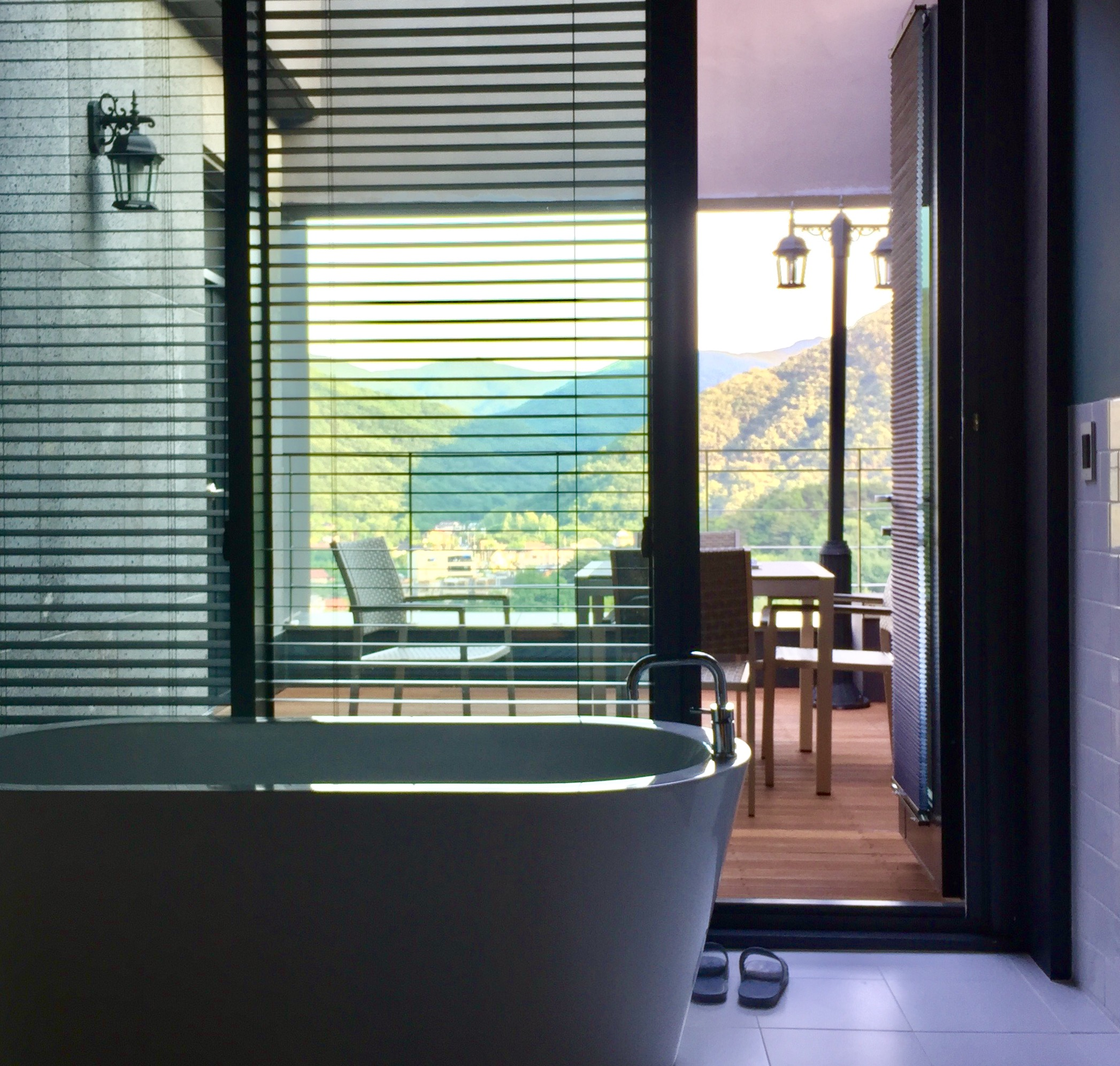 Relaxing view of the in-room bathtub with a balcony beyond.
