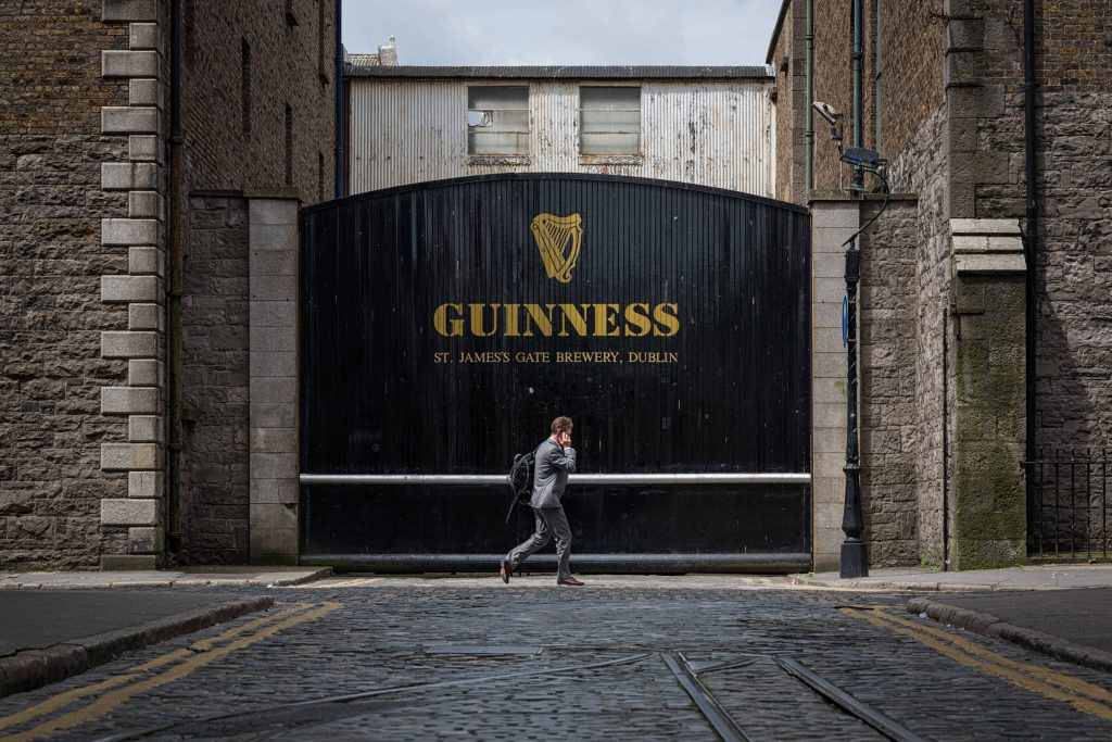 A man walks in front of the famous Guinness gates in Dublin.