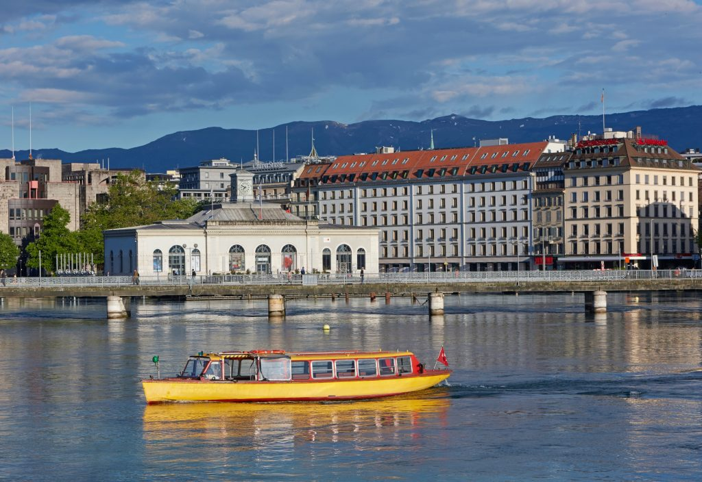 A yellow water taxi on the shoreline of Geneva.