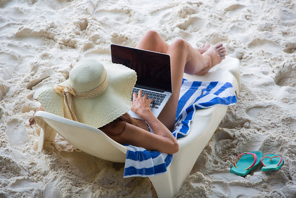 Many travellers on holidays find it hard to switch off online. Image: EyesWideOpen/Getty Images