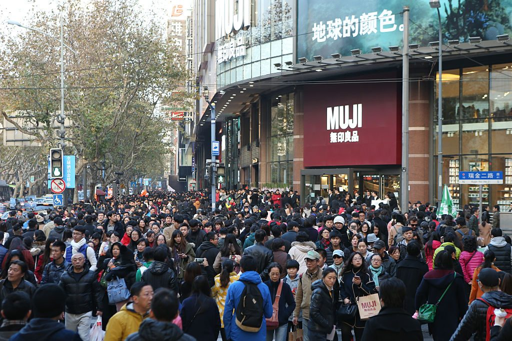 People wait to enter the world's largest MUJI flagship store on December 12, 2015 in Shanghai, China.