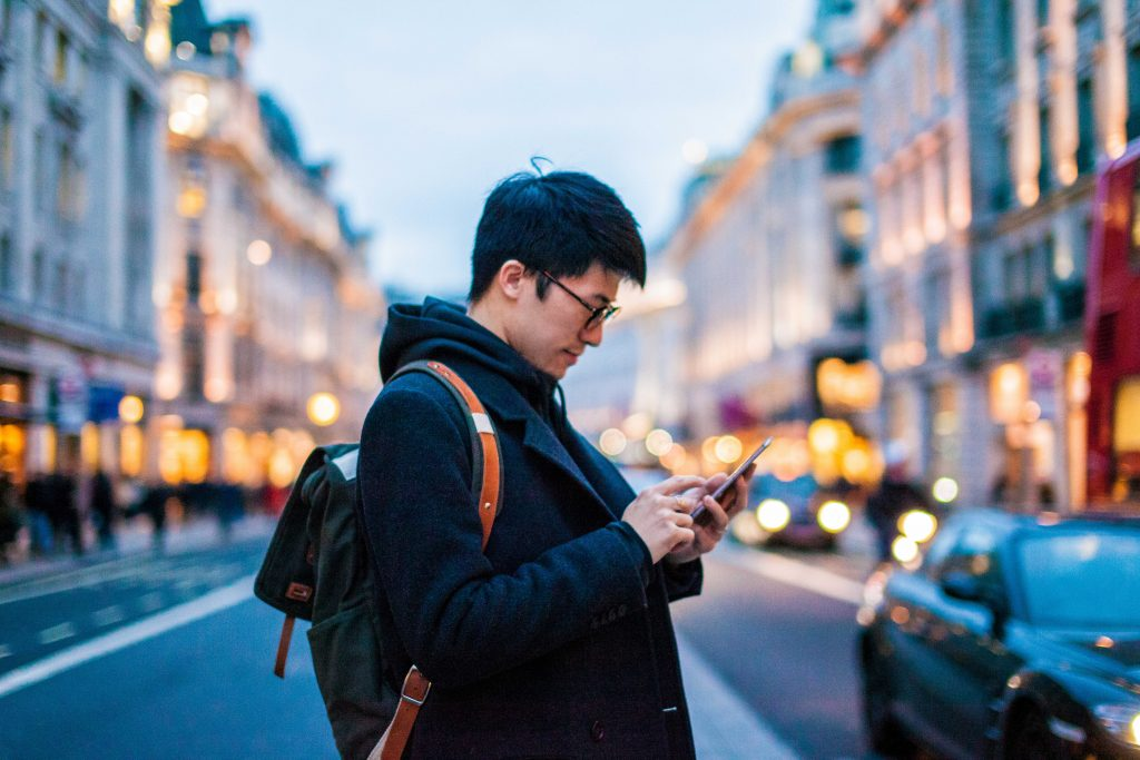 Young man using mobile phone on the street.