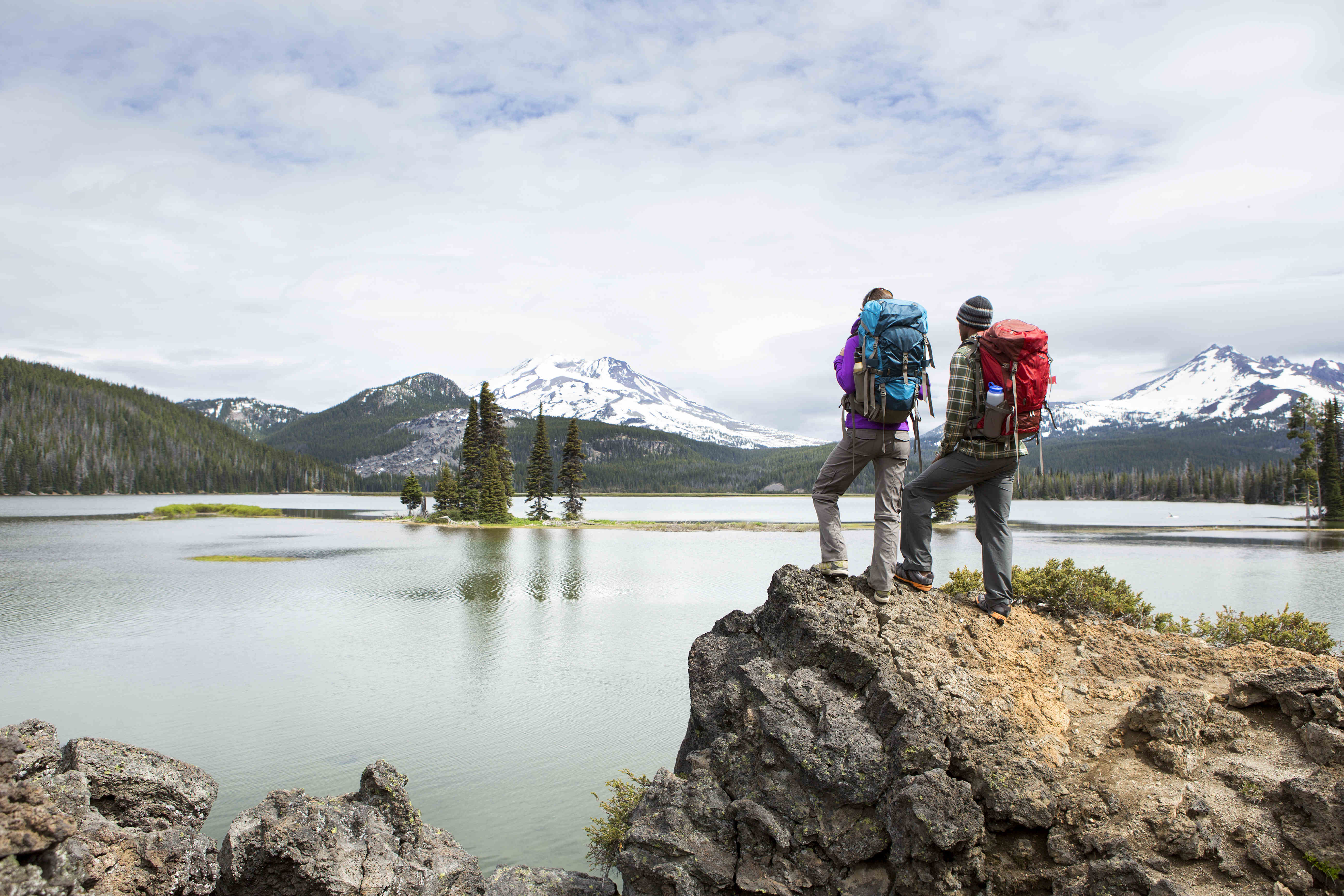 Hikers stand on a rock in Oregon.