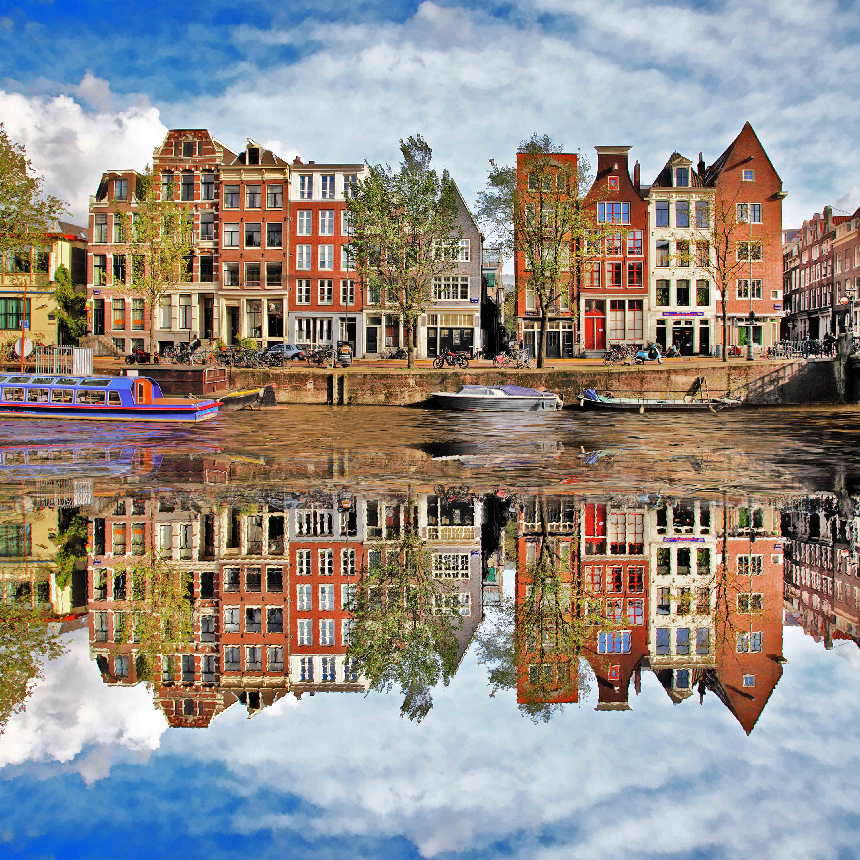 An Amsterdam street with its reflection in water.