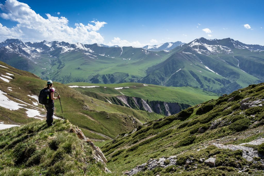 A person hikes on high hills in the mountains of Kyrgyzstan.