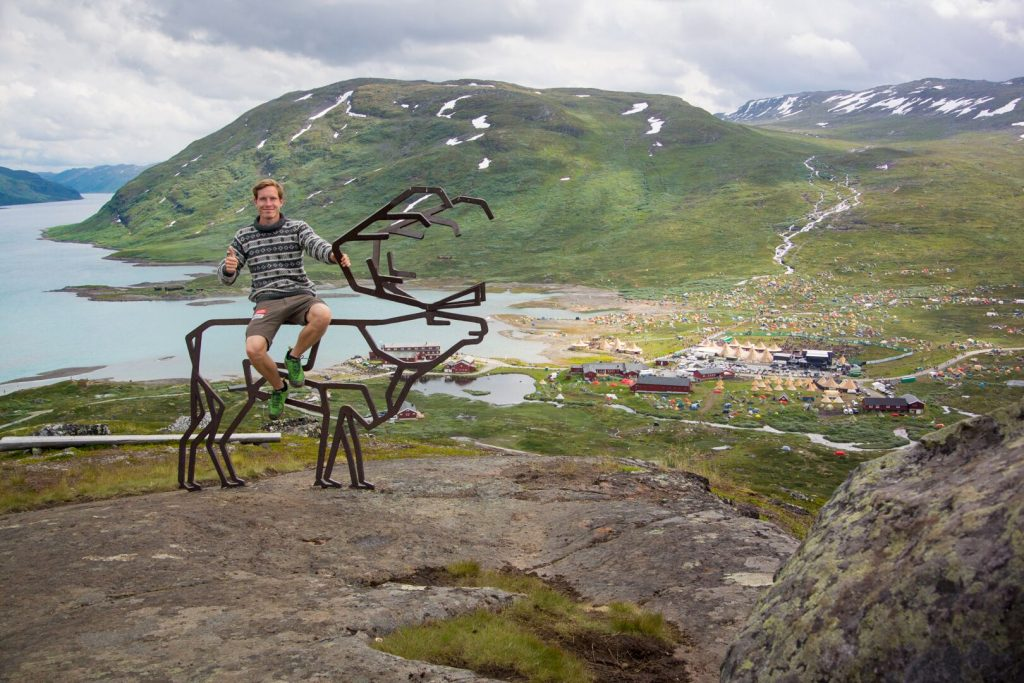 Andreas Orset sits in front of a festival scene in the Norwegian countryside.