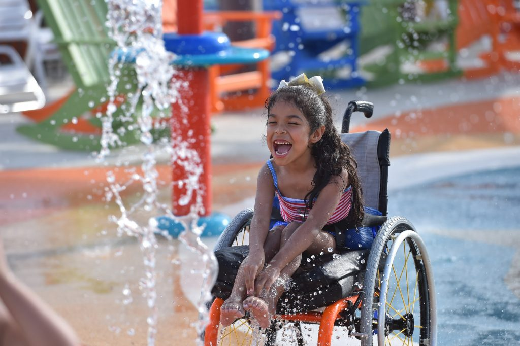 A little girl in a wheelchair enjoys the park preview