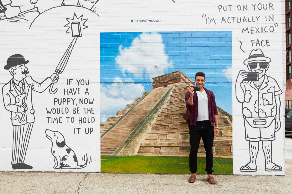 A man poses in front of the Mexico artwork on the Dating Wall