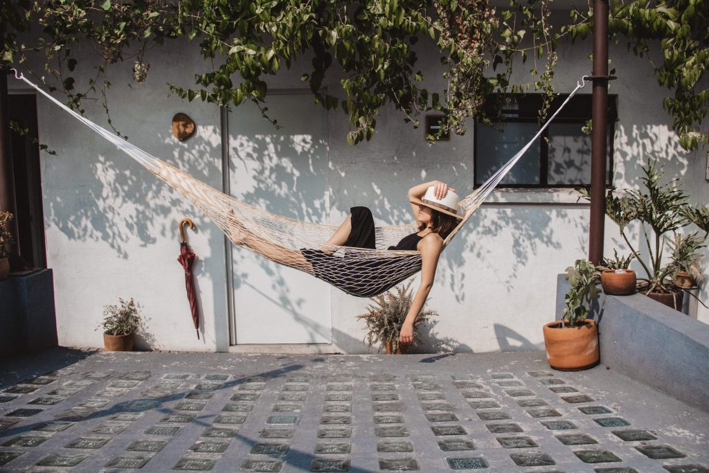 Woman Relaxing In Hammock Against Wall At Yard.