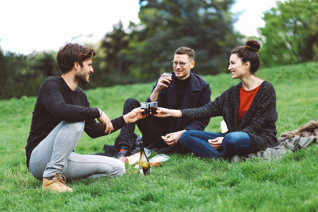 Image of a young group of friends, sitting in Parc des Buttes Chaumont park in the northeastern part of Paris, having a picnic, toasting with red wine, having fun and relaxing in the nice springtime day.