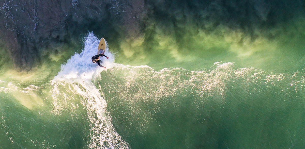 A man surfs on a green wave in Perth, Australia.