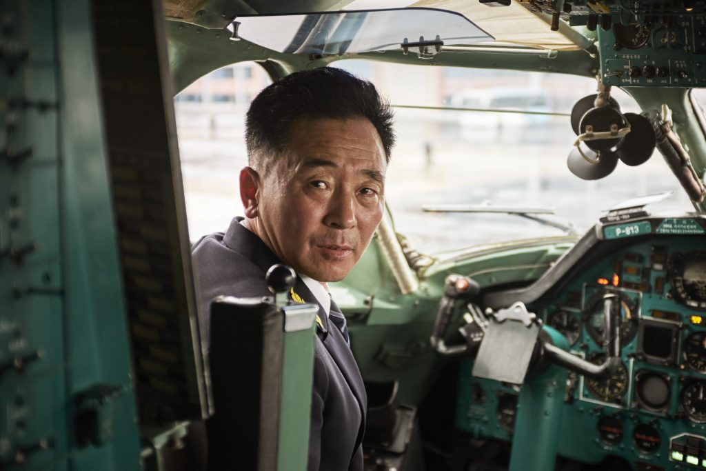 An Air Koryo pilot looks back from the cockpit of an aircraft.