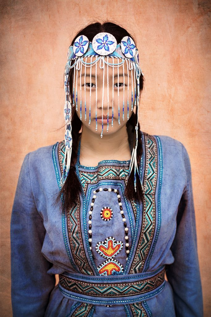 A girl poses for the camera in traditional Evenki clothing.
