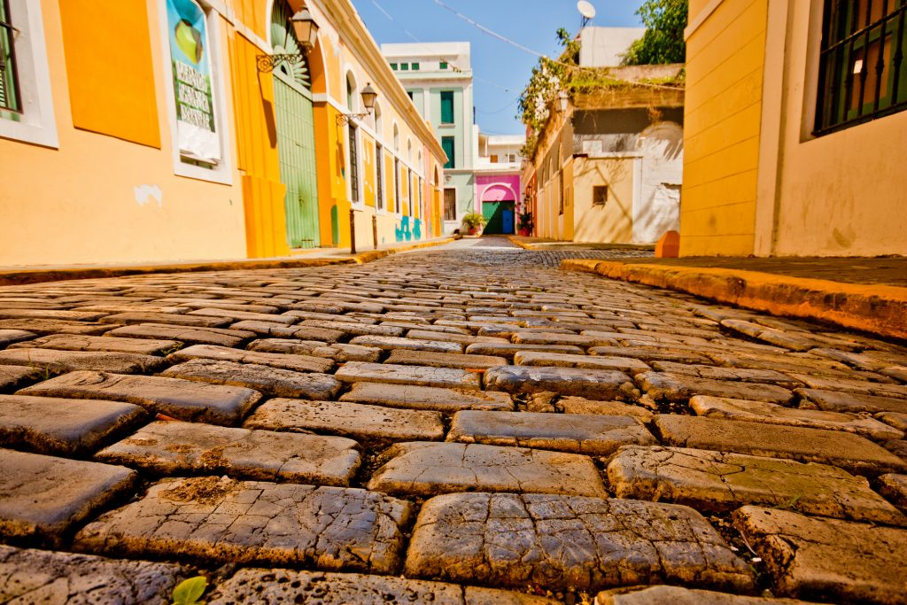 Old tiled street in old San Juan downtown, Puerto Rico. Colorful buildings around give it very vivid and alive feel under noon sun.