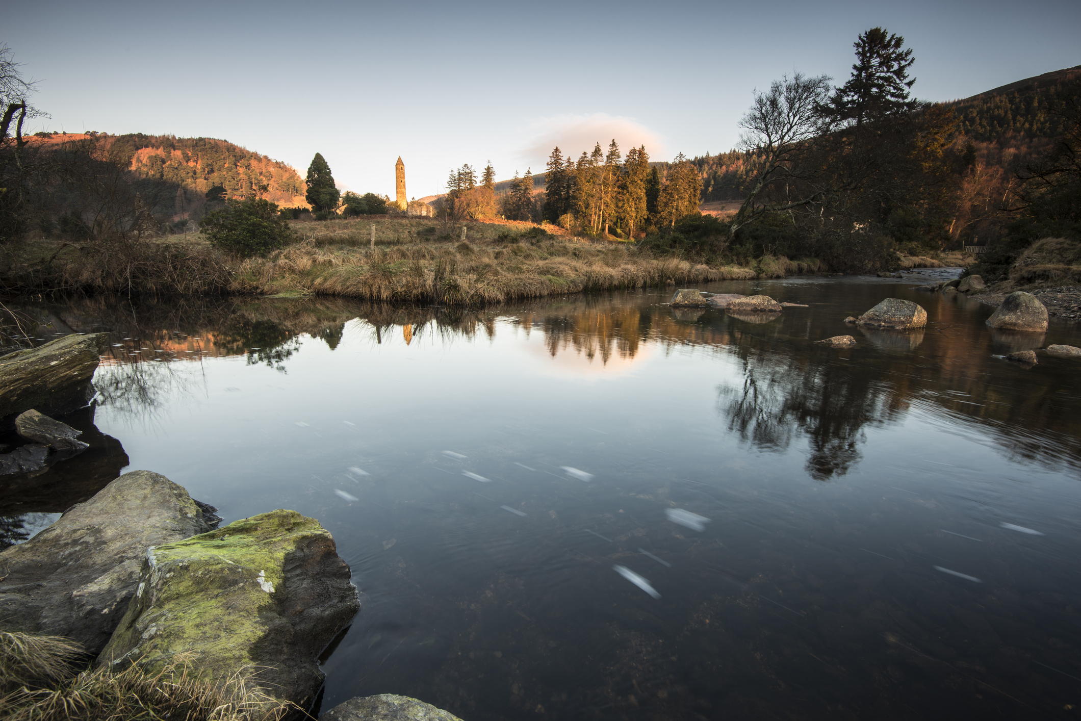 Sunrise over the ruins of Glendalough as the smooth waters of the river reflect the beautiful scenery of the Wicklow Mountains National Park.