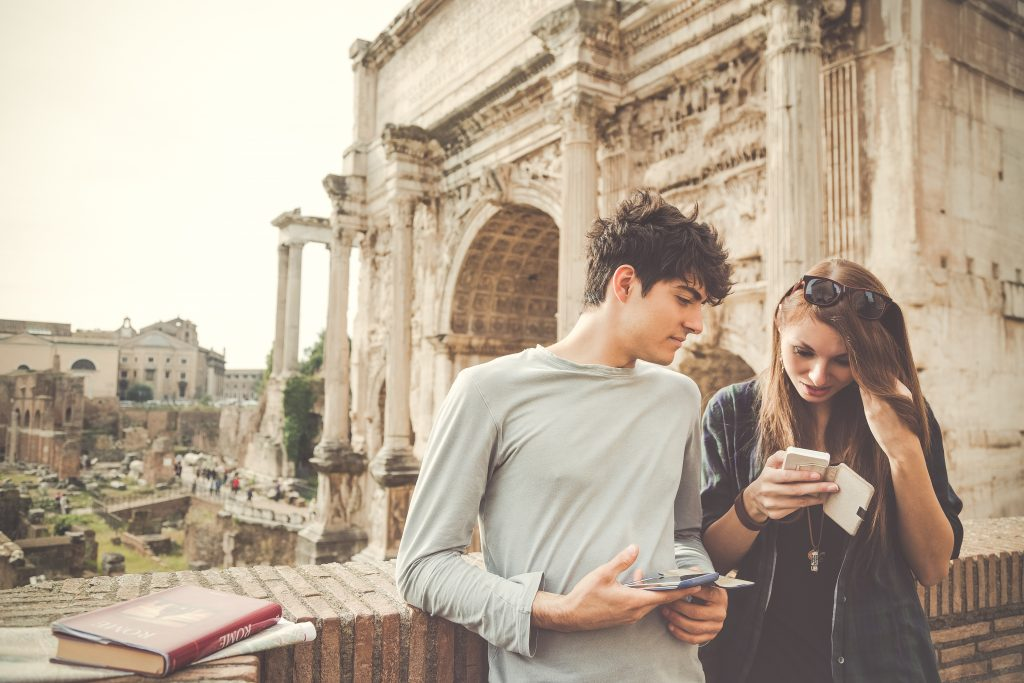 A couple looking at smartphones in Rome