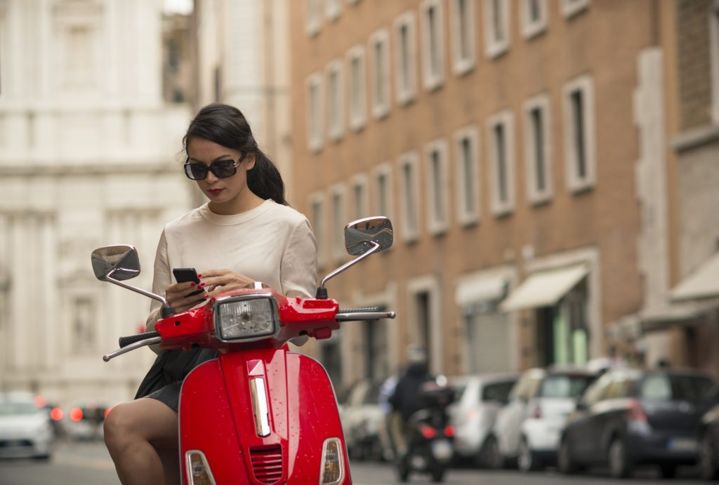 A woman on a moped in Rome using a smartphone
