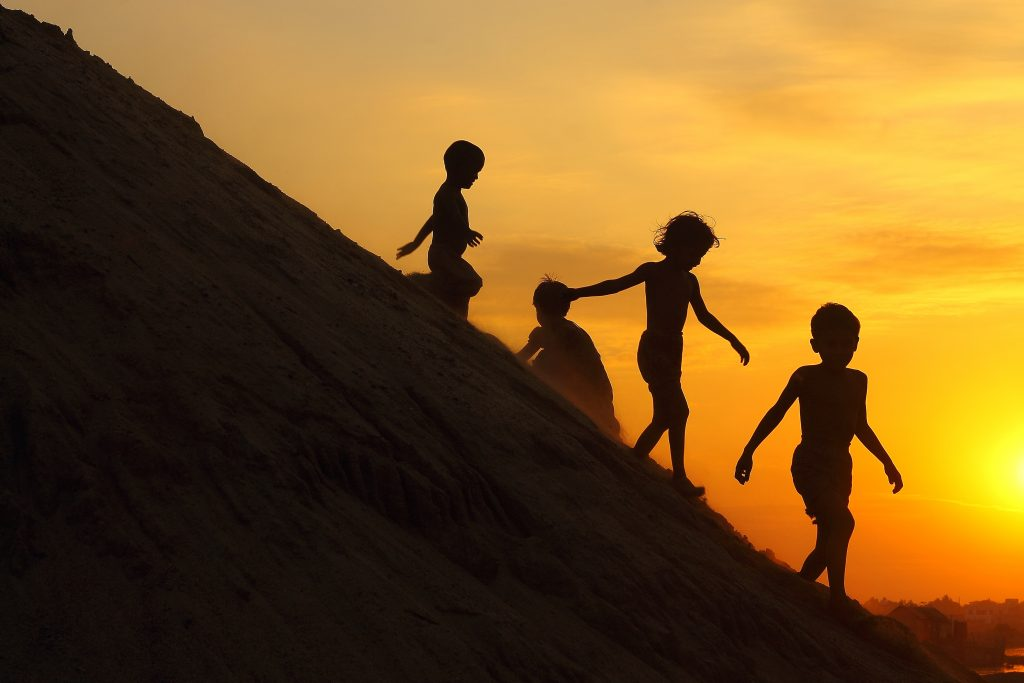 Children in Bangladesh against the backdrop of the setting sun.